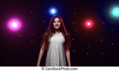 Girl with long hair whirling against disco lights. Slow Motion