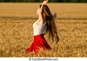 Girl with long hair whirling in a wheat field arms spread