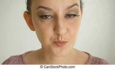 Girl with long lashes and brown eyes makes air kiss. Cute...