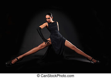 girl with long legs against black background