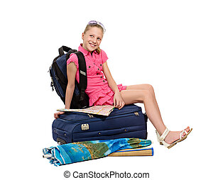 girl with luggage and map sitting on a suitcase