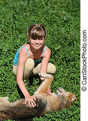 Girl with lying dog