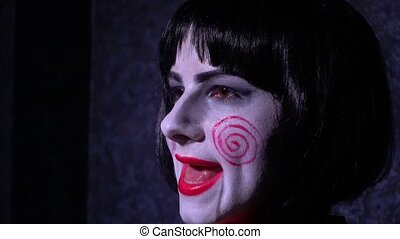 Girl with make-up in nightmare style sings on a black...