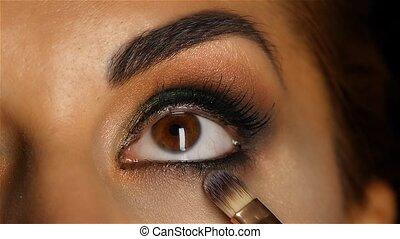 Girl with make up looking up, visagiste brush adjusts her mak eup. Close up. Slow motion