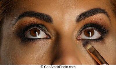 Girl with make up looking up, visagiste brush adjusts her make up. Close up. Slow motion