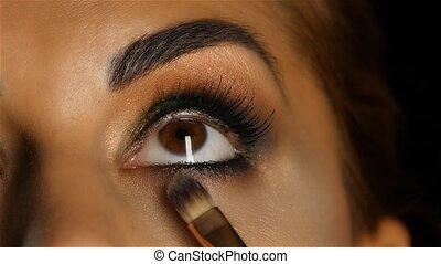 Girl with make up looking up, visagiste brush adjusts her makeup. Close up. Slow motion