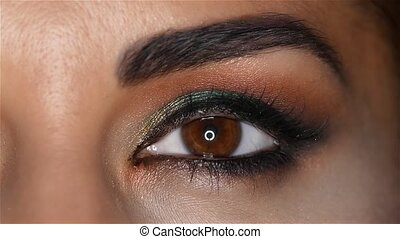 Girl with make up looks fascinating look and blinks. Close...