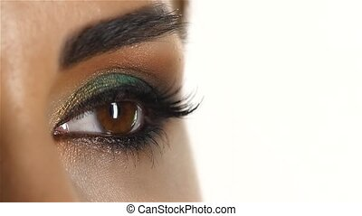 Girl with makeup and eye closed and opens it blinks. Close up. Slow motion