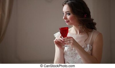 Girl with makeup in a pink wedding dress is sitting in a beautiful room surrounded by flowers and candles