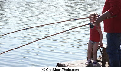 Girl with man fishing - On wooden pier granddaughter and...