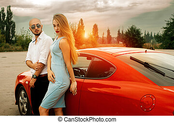 girl with man posing at sunset with sport car