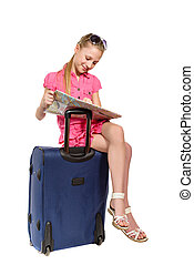 girl with map sitting on a suitcase