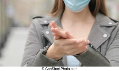 Young girl with mask cleaning hands with alcohol sanitizer in the street