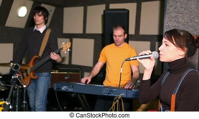 girl with microphone singing in studio, musicians against