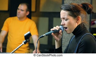 girl with microphone singing in studio