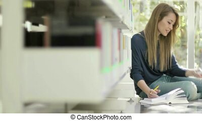 Girl with mobile phone in library - Female blonde college...