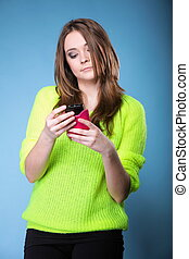 Girl with mobile phone smartphone reads message studio shot blue background