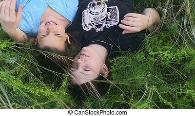 girl with mother lying in the grass slow motion video