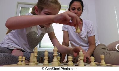 Girl with mother near chessboard
