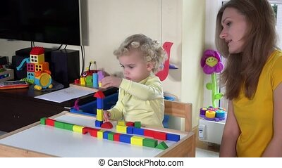 girl with mother playing colorful wooden bricks near small table at home