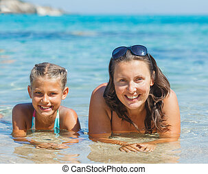 Girl with mother swimming in sea