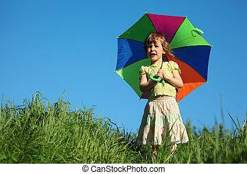girl with  multicoloured umbrella in grass
