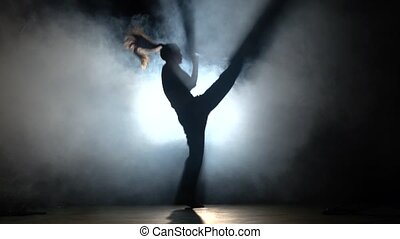 Girl with muscled body. Training martial arts. Black. Silhouette. Backlight