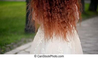 Girl with natural red curly hair.A natural beauty. A little wind ruffles your hair
