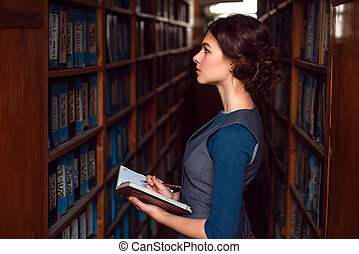 Girl with notebook select textbook in library.