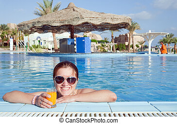 Girl with orange juice at resort hotel