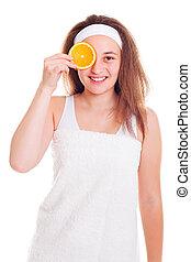 Girl with orange slice over her eye