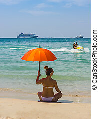 girl with orange umbrella on the beach in Thailand