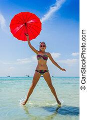 girl with orange umbrella on the beach in Thailand