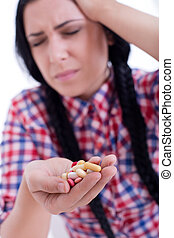 Girl with pains holding pills