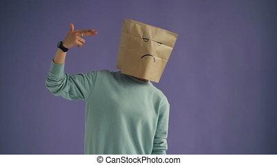 Girl with paper bag on head making gun gesture shooting...