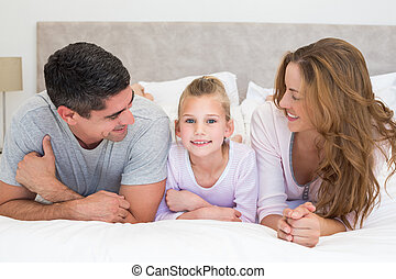 Girl with parents in bed