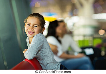 girl with parents waiting for flight