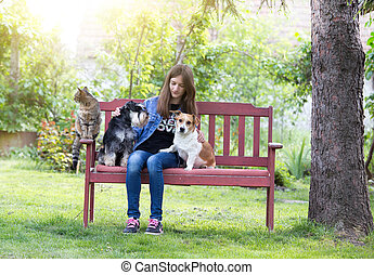 Girl with pets in park - Teenage girl with dogs and cat...
