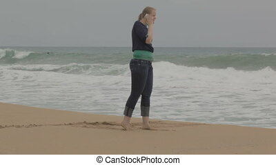 Girl with phone at the beach.