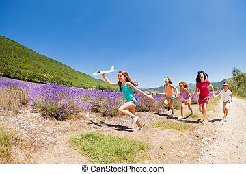 Girl with plane model running before her friends