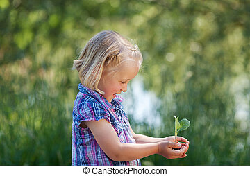 Girl with plant - Young cheerful girl holding a little plant...