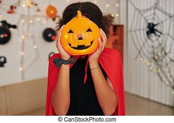 Girl with plastic jack o lantern
