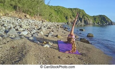 Girl with Ponytail in Yoga Pose against Seascape in Morning...