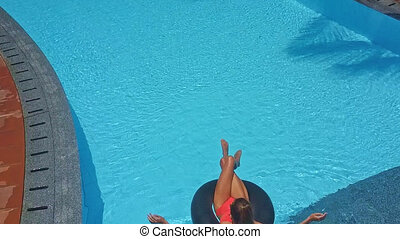 girl with ponytail swims on ring in pool - backside view...