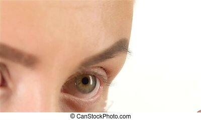 Girl with poor vision puts lens and flashes. Close up. White background. Slow motion