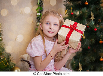 Girl with present box wondering at Christmas