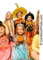 Girl with pumpkin, friends in Halloween costume