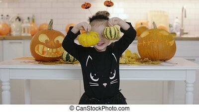 Girl with pumpkins - Smiling little girl in cute Halloween...