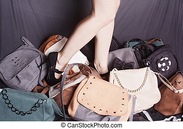 Girl with purse - Girl standing in a pile of bags against ...