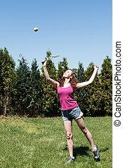 Girl with racket and ball on backyard